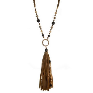 """Brown braided cord necklace with a large faux leather pendant and neutral colored beads. Approximately 36"""" in length."""