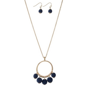 """Gold tone necklace set with an open circle pendant, navy blue thread wrapped wrapped bead fringe, and matching fishhook earrings. Approximately 32"""" in length."""