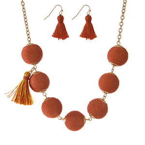 "Gold tone necklace set with orange thread wrapped beads, tassel accents and matching fishhook earrings. Approximately 16"" in length."