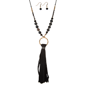 """Gold tone necklace set with a navy blue faux leather tassel, a beaded chain and matching fishhook earrings. Approximately 32"""" in length."""