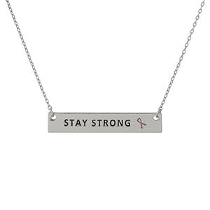 "Dainty silver tone, Breast Cancer Awareness necklace with a bar pendant, stamped with ""Stay Strong."" Approximately 16"" in length."