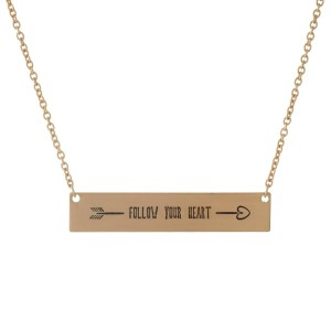 "Dainty gold tone necklace with a bar pendant, stamped with ""Follow Your Heart."" Approximately 16"" in length."