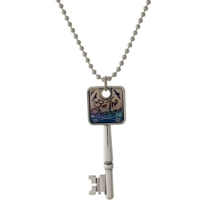 """Silver tone necklace with a key pendant that says """"Be The Change."""" Approximately 26"""" in length."""