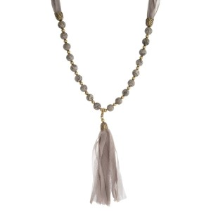 "Burnished gold tone necklace with gray beads and a fabric tassel. This can be worn as a wrap bracelet by unclipping the tassel. Approximately 32"" in length."