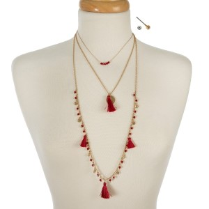 "Gold tone three layer necklace with crimson beads and tassels. Approximately 14"" to 32"" in length."