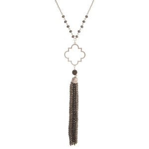 "Silver tone necklace with an open quatrefoil shape and a beaded tassel. Approximately 32"" in length."