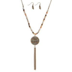 "Gold tone necklace set with a half beaded body, a circle pendant stamped with ""Happy Camper"" and a chain tassel. Approximately 32"" in length."