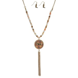 """Gold tone necklace set with a half beaded body, a circle pendant stamped with """"Y'all"""" and a chain tassel. Approximately 32"""" in length."""