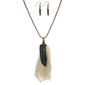 """Copper tone necklace with a patina feather pendant, an ivory fabric tassel and matching fishhook earrings. Approximately 32"""" in length."""