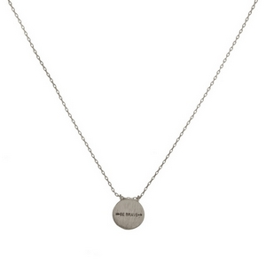 """Dainty metal necklace with a circle pendant stamped with an arrow and """"Be Brave."""" Approximately 16"""" in length."""