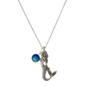 "Long, silver tone necklace with a mermaid pendant and a rhinestone pendant. Approximately 32"" in length."