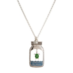 "Silver tone necklace with a mason jar pendant and a beach theme. Approximately 30"" in length."