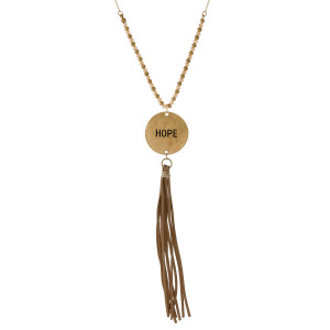 "Dainty necklace with a coin pendant, stamped with ""Hope"" and accented by a faux leather tassel. Approximately 32"" in length."
