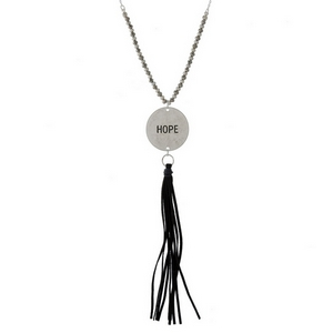 """Dainty necklace with a coin pendant, stamped with """"Hope"""" and accented by a faux leather tassel. Approximately 32"""" in length."""