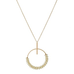 """Gold tone necklace with a wire-wrapped, pearl beaded, open circle pendant. Approximately 30"""" in length."""