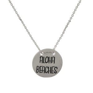 "Dainty metal necklace with a circle pendant stamped with ""Aloha Beaches."" Approximately 16"" in length."