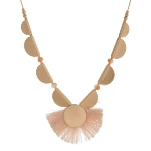 "Gold tone necklace with a burnished, scalloped design and a fanned tassel pendant. Adjustable up to 32"" in length."
