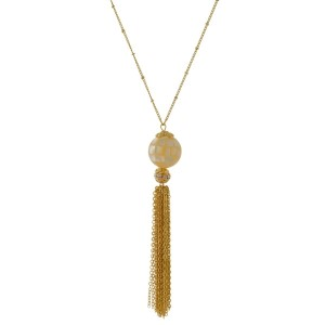 "Gold tone necklace with a natural stone, ball pendant and a chain tassel. Approximately 32"" in length."