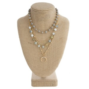 """Gold tone layered necklace with natural stone beads, faceted beads, and horn pendant. Approximately 18"""" in length."""