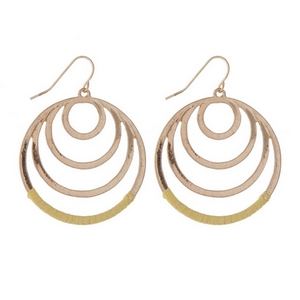 "Gold tone fishhook earrings with cascading circles and yellow thread. Approximately 1.25"" in length."