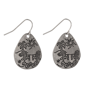 "Silver tone teardrop shaped earrings stamped with a beach scene. Approximately 1"" in length."