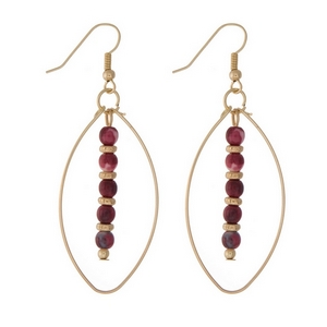 """Gold tone fishhook earrings with an open oval shape and burgundy beads. Approximately 2"""" in length."""