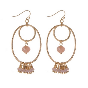 "Gold tone fishhook earrings with an open oval shape and pale pink faceted beads. Approximately 2"" in length."