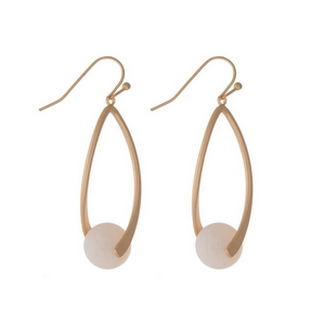 "Matte gold tone fishhook earrings with an oval shape and a peach natural stone bead. Approximately 1.5"" in length."