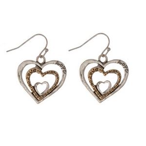 """Silver tone fishhook earrings displaying two tone heart shapes, stamped with """"love."""" Approximately 1"""" in length."""
