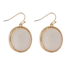 """Gold tone fishhook earrings displaying a mother of pearl circle shape. Approximately 1"""" in diameter."""
