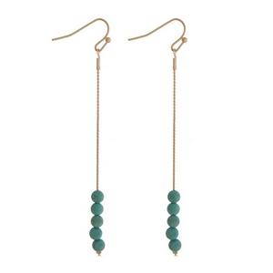 """Gold tone fishhook earrings with turquoise natural stone beads. Approximately 3"""" in length."""