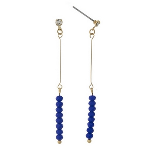 """Dainty gold tone stud earrings featuring royal blue faceted beads. Approximately 2"""" in length."""