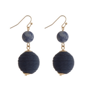 "Gold tone fishhook earrings featuring a sodalite natural stone and a navy blue thread wrapped ball. Approximately 1.5"" in length."