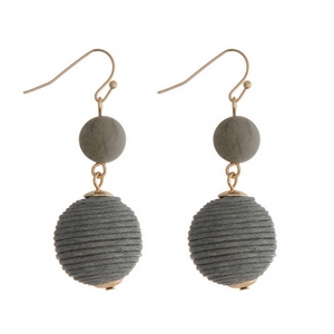 "Gold tone fishhook earrings featuring a gray natural stone and a gray thread wrapped ball. Approximately 1.5"" in length."