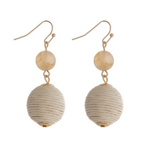 "Gold tone fishhook earrings featuring a beige natural stone and an ivory thread wrapped ball. Approximately 1.5"" in length."