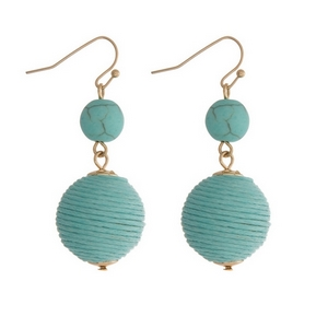 "Gold tone fishhook earrings featuring a turquoise natural stone and a mint green thread wrapped ball. Approximately 1.5"" in length."