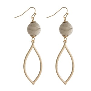 """Gold tone fishhook earrings with an ivory thread wrapped ball and an open teardrop shape. Approximately 2.5"""" in length."""