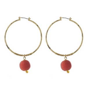 """Gold tone hoop earrings with a red thread wrapped bead. Approximately 2"""" in diameter."""