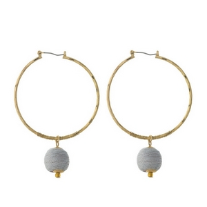 """Gold tone hoop earrings with a gray thread wrapped bead. Approximately 2"""" in diameter."""