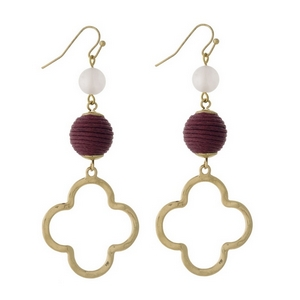 "Gold tone fishhook earrings with a burgundy thread wrapped bead and an open clover shape. Approximately 3"" in length."