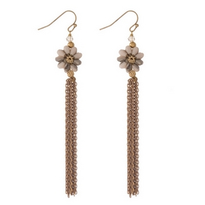 "Gold tone fishhook earrings with a neutral beaded flower and chain fringe. Approximately 4"" in length."