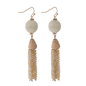 """Gold tone fishhook earrings with an ivory thread wrapped bead and a beaded tassel. Approximately 3"""" in length."""