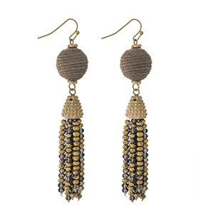 """Gold tone fishhook earrings with a brown thread wrapped bead and a beaded tassel. Approximately 3"""" in length."""