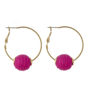 """Gold tone hoop earrings with a lever back and a pink thread wrapped bead. Approximately 1.5"""" in diameter."""