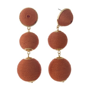 "Gold tone post style earrings with orange thread wrapped beads. Approximately 3"" in length."