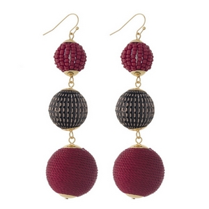 """Gold tone fishhook earrings with burgundy thread wrapped and beaded, beads. Approximately 3.5"""" in length."""