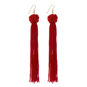 "Gold tone fishhook earrings with a red knotted bead and thread tassel. Approximately 5"" in length."