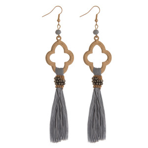 "Gold tone fishhook earrings with an open clover shape and a thread tassel. Approximately 5"" in length."