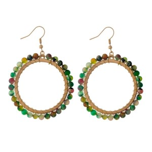 "Gold tone, open circle, fishhook earrings with wire wrapped hunter green natural stones. Approximately 2"" in diameter."