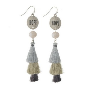 "Fishhook earrings with a circle shape stamped with ""Hope"" and a tiered metallic tassel. Approximately 3.5"" in length."